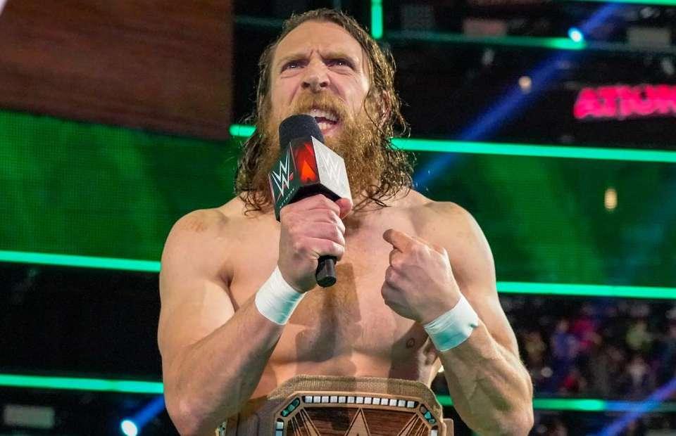 Daniel Bryan está no ringue, segurando o microfone com a mão direita. Com a mão esquerda aponta para si mesmo. Sua expressão facial é de raiva.