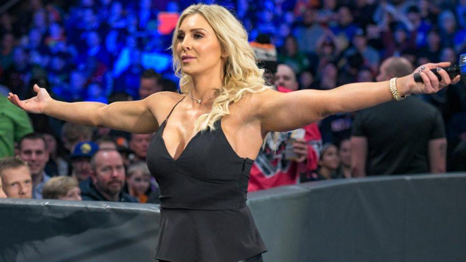 Fotografia mostra em primeiro plano Charlotte Flair, com os braços abertos, olhado para um lado da plateia. No fundo, o outro lado da plateia, iluminada de azul pelo efeito de luz da arena.